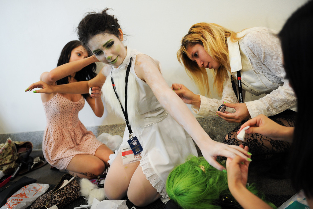 ". Hannah Forbes gets a make-up job from friends for her character ""Jade Sprite\"" at the Anime Expo at the L.A. Convention Center, Saturday, July 6, 2013. (Michael Owen Baker/L.A. Daily News)"