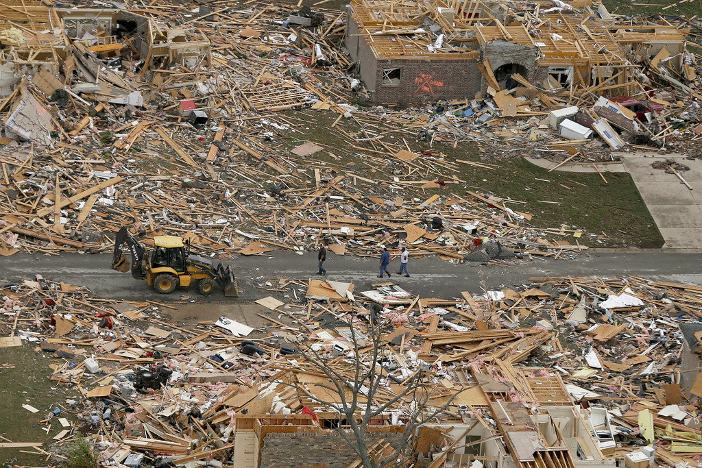 . People walk between two destroyed houses in Mayflower, Ark., Monday, April 28, 2014, after a tornado struck the town late Sunday. (AP Photo/Danny Johnston)