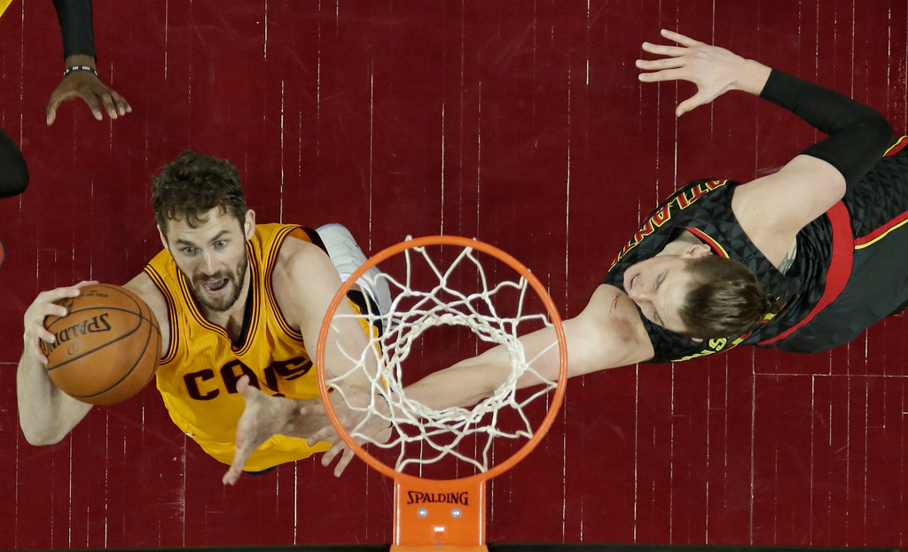 . Cleveland Cavaliers\' Kevin Love, left, drives to the basket against Atlanta Hawks\' Mike Muscala in the second half of an NBA basketball game, Friday, April 7, 2017, in Cleveland. (AP Photo/Tony Dejak)