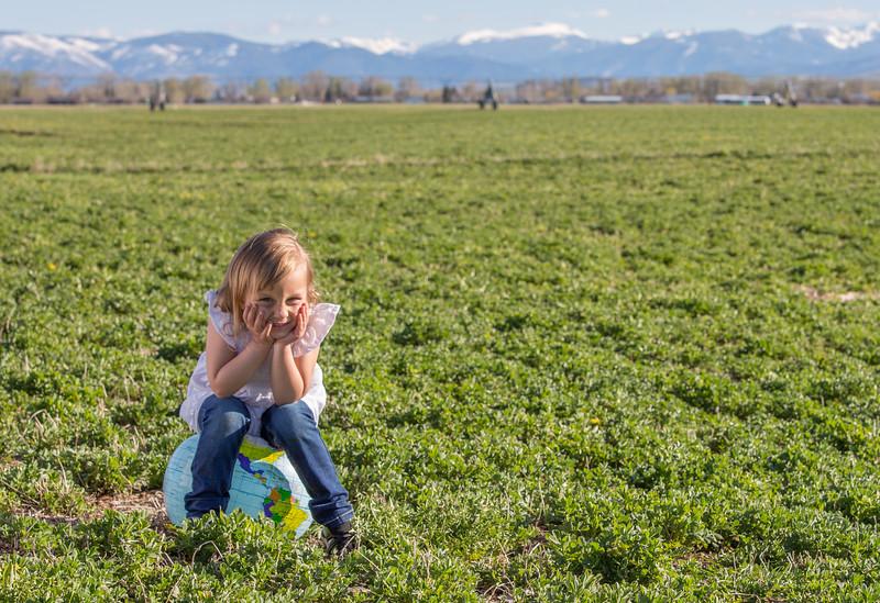 Little girl sitting on a world globe.