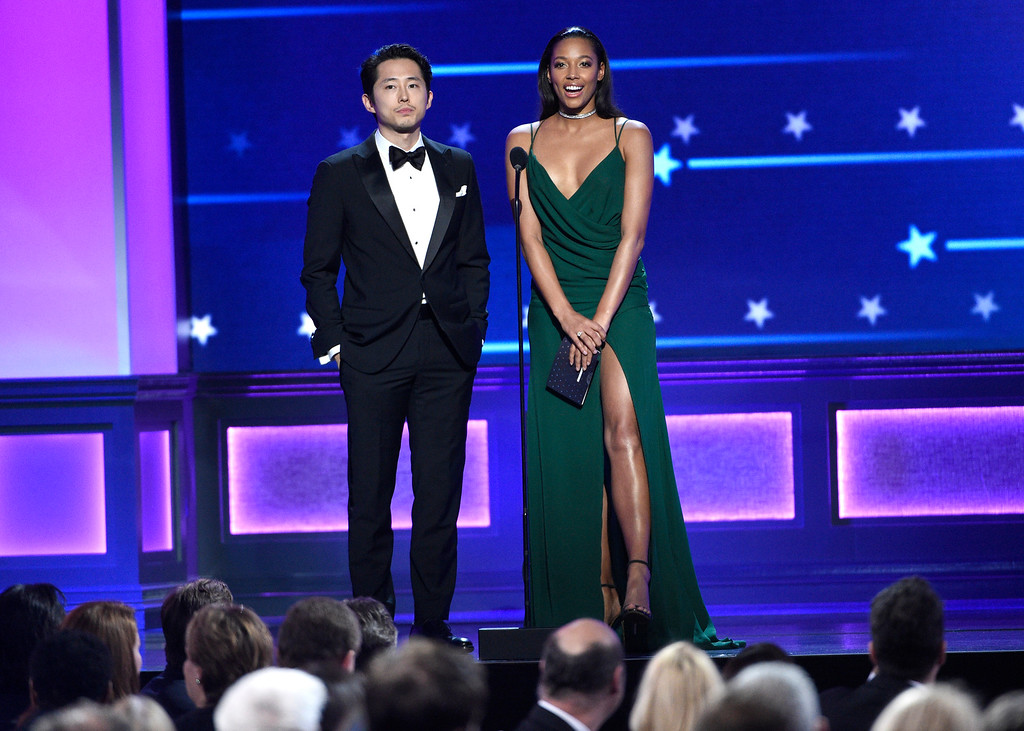 . Steven Yeun, left, and Kylie Bunbury present the award for best actress in a comedy series at the 22nd annual Critics\' Choice Awards at the Barker Hangar on Sunday, Dec. 11, 2016, in Santa Monica, Calif. (Photo by Chris Pizzello/Invision/AP)