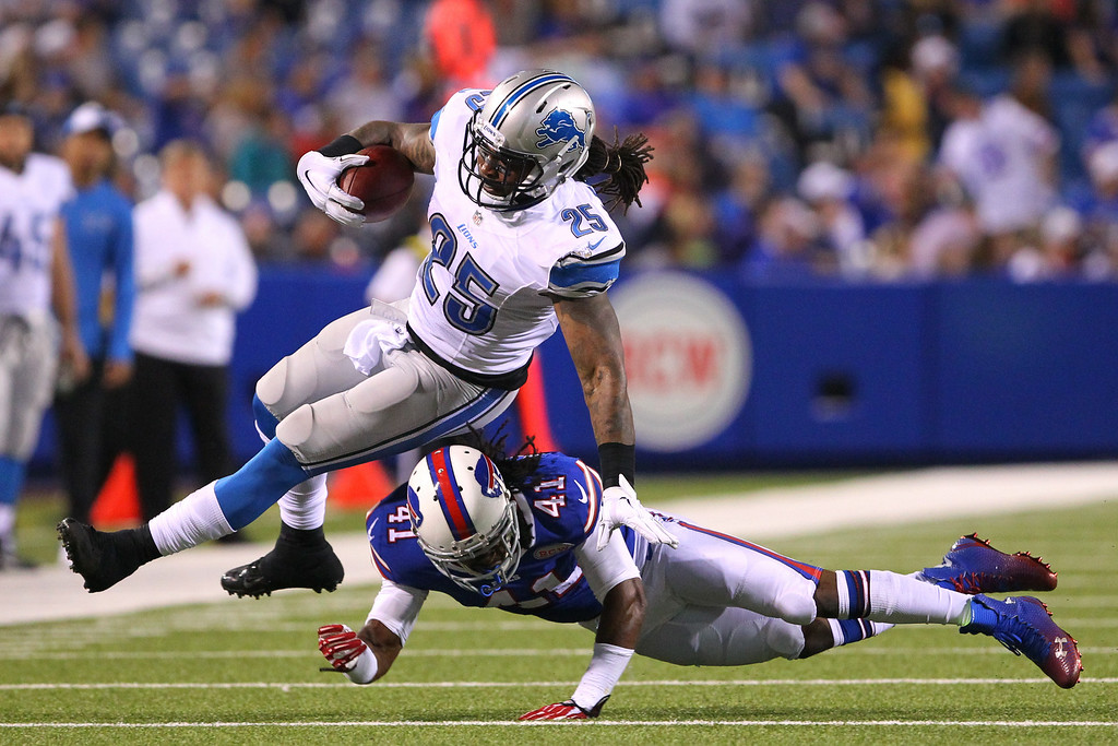 . Detroit Lions\' Mikel Leshoure (25) is tripped up by Buffalo Bills defensive back Kamaal McIlwain (41) during the second half of a preseason NFL football game, Thursday, Aug. 28, 2014, in Orchard Park, N.Y. (AP Photo/Bill Wippert)