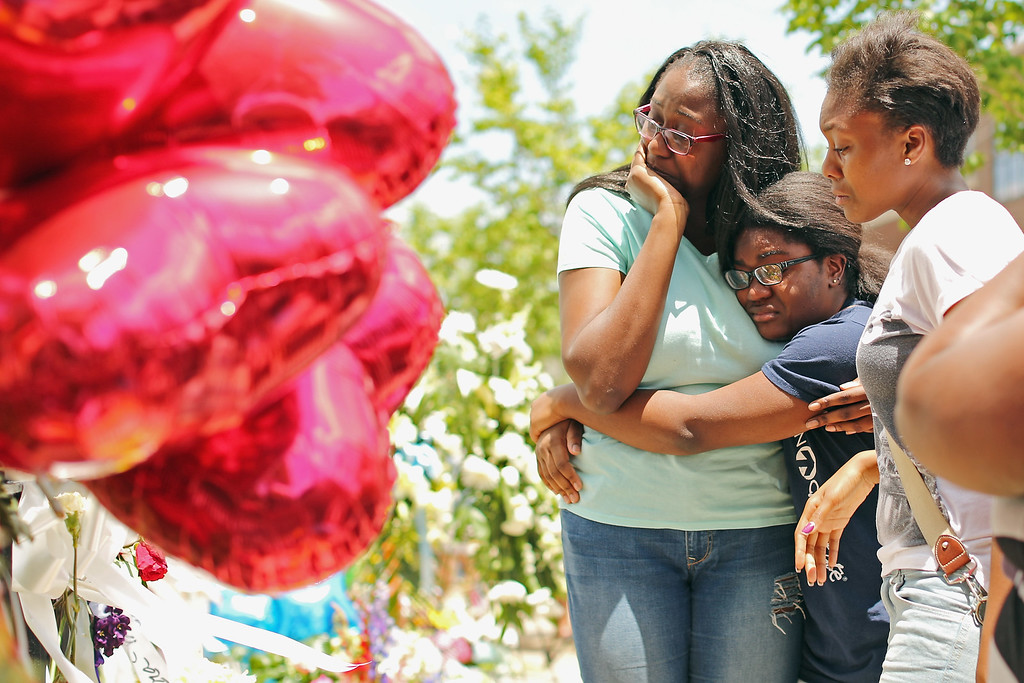 . Relatives of Rev. Depayne Middleton Doctor embrace and weep while visiting makeshift memorial outside the historic Emanuel African Methodist Church where Doctor and eight others were shot to death June 20, 2015 in Charleston, South Carolina. Members of the church announced that services and Sunday school will go ahead as scheduled tomorrow. Suspect Dylann Roof, 21, was arrested and charged in the killing of nine people during a prayer meeting in the church, one of the nation\'s oldest black churches in the South.  (Photo by Joe Raedle/Getty Images)
