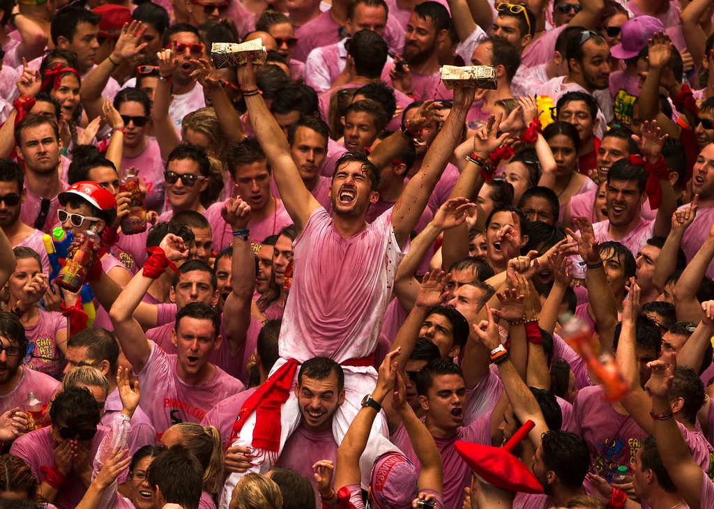 """. Revelers throw wine before the launch of the \""""Chupinazo\"""" rocket, to celebrate the official opening of the 2014 San Fermin fiestas in Pamplona, Spain, Sunday, July 6, 2014. Revelers from around the world turned out to kick off the festival with a messy party in the Pamplona town square, one day before the first of eight days of the running of the bulls glorified by Ernest Hemingway\'s 1926 novel \""""The Sun Also Rises.\"""" (AP Photo/Andres Kudacki)"""
