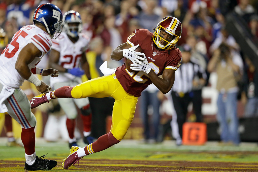 . Washington Redskins wide receiver Andre Roberts (12) pulls in a touchdown pass under pressure from New York Giants free safety Quintin Demps (35) during the first half of an NFL football game in Landover, Md., Thursday, Sept. 25, 2014. (AP Photo/Patrick Semansky)