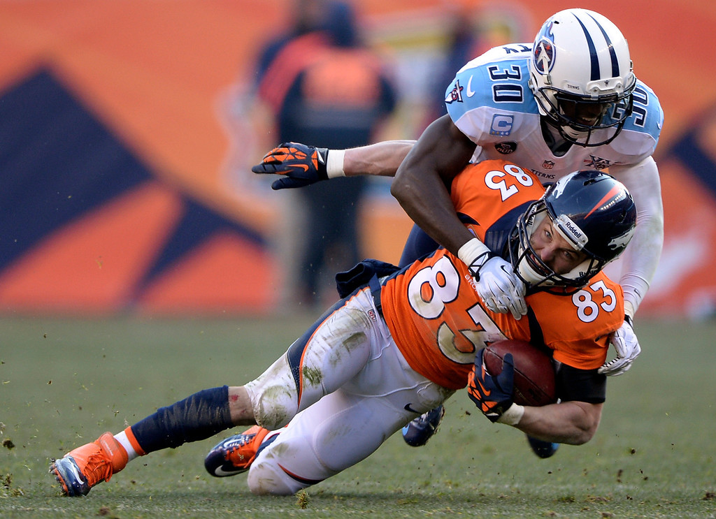 . Denver Broncos wide receiver Wes Welker (83) gets wrapped up and taken down by Tennessee Titans cornerback Jason McCourty (30) during the first half.  (Photo by Hyoung Chang/The Denver Post)