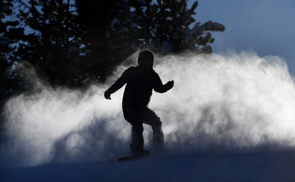 . A snowboarder, silhouetted by the setting sun, kicks up a wake of snowy mist, at Winter Park alpine resort, in Colorado, Thursday Dec. 20, 2012. Fresh snow earlier in the week, with more expected before Christmas, has left much of Colorado ski-country replenished after a relatively warm and dry Fall. (AP Photo/Brennan Linsley)