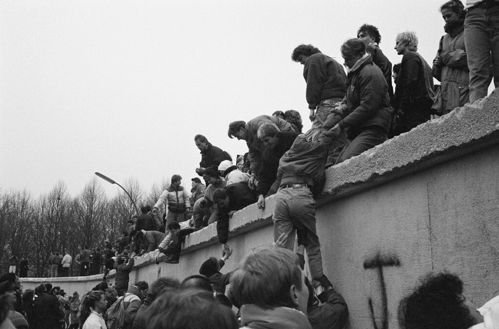 . East Berliners climb onto the Berlin Wall to celebrate the effective end of the city\'s partition, 31st December 1989. (Photo by Steve Eason/Hulton Archive/Getty Images)