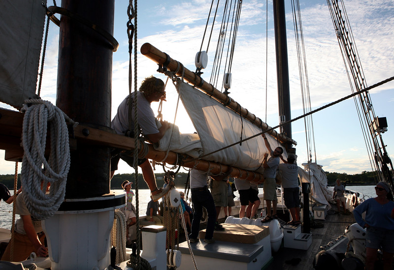 AMY SWEENEY/Staff photo  McKinley Halpern-Reiss, left, one of the crew members takes down the sails.   The National Historic Landmark Schooner Adventure is commissioned and sailing once again from Gloucester's harbor. ORG XMIT: nsob0v77