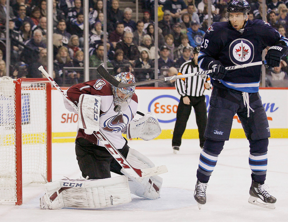 . Winnipeg Jets\' Blake Wheeler (26) attempts to deflect the shot past Colorado Avalanche\'s goaltender Semyon Varlamov (1) during second period NHL action in Winnipeg, Manitoba, on Thursday, Dec. 12, 2013. (AP Photo/The Canadian Press, John Woods)