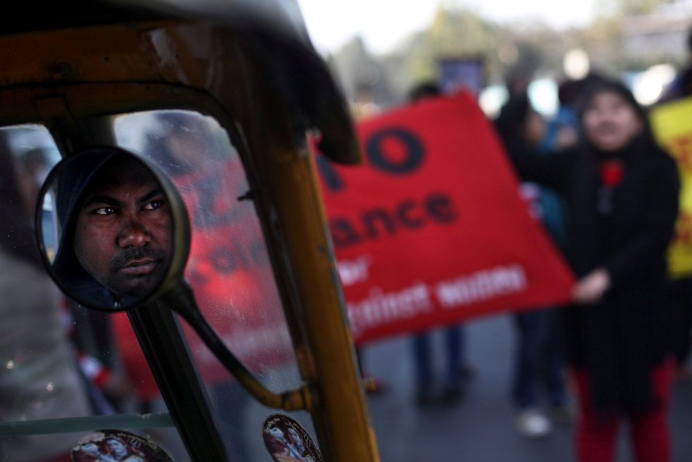 . Face of an Indian auto-rickshaw driver is reflected on the side mirror as he watches protesters block a main road outside the Delhi Police headquarters during a protest in New Delhi, India, Wednesday, Dec. 19, 2012. The hours-long gang-rape and near fatal beating of a 23-year-old physical therapy student in a bus in New Delhi triggered outrage and anger across the country Wednesday as Indians demanded action from authorities who have long ignored persistent violence and harassment against women. (AP Photo/Altaf Qadri)