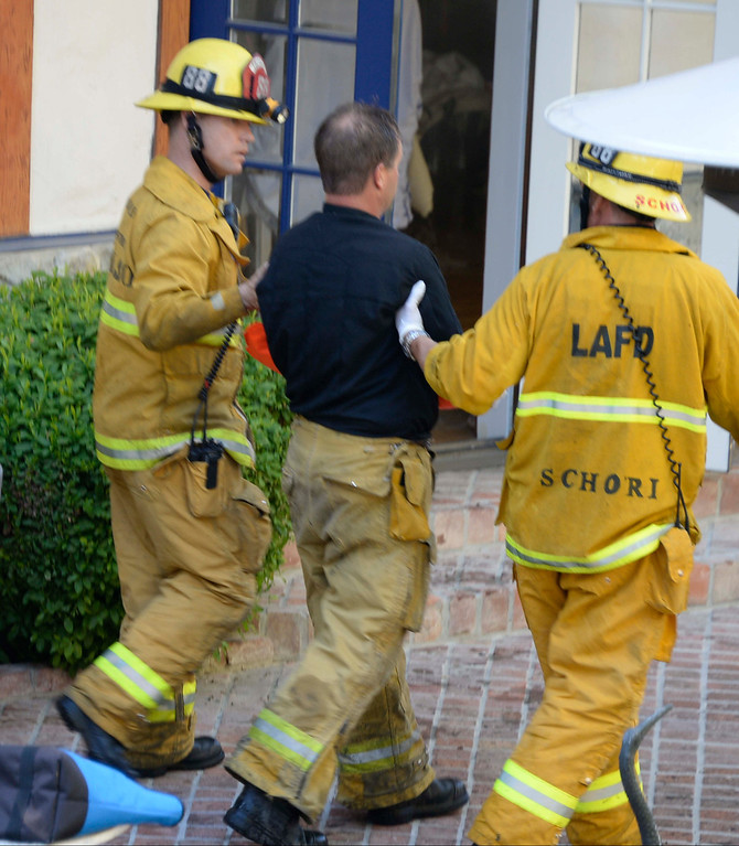 . LA city firefighters help a fellow firefighter who fell through a wooden stair case and suffered a writs and rib injury at a fire that broke out this afternoon in a three-story home in a hilly, inaccessible area of Encino left one firefighter injured and heavily damaged the large residence.  About 75 firefighters were initially dispatched at 3:37 p.m. to the 4400 block of Balboa Avenue, said Erik Scott of the Los Angeles Fire Department. Nearly an hour later, about 100 personnel were on scene and appeared to be getting a handle on the blaze, which began on the top floor.  It was not clear how seriously the firefighter was injured or what sparked the blaze. Oct 30,2013. Encino CA. Photo by Gene Blevins