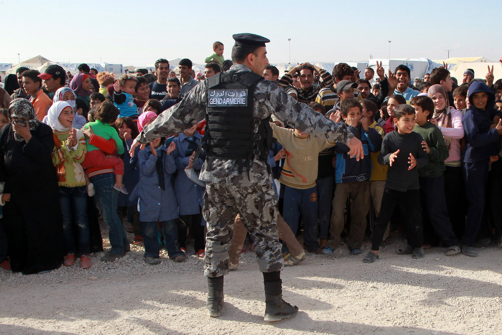 Description of . A Jordanian Gendarmerie officer gestures as Syrian refugees react during United Nations (U.N.) Secretary-General Ban Ki-moon's arrival to visit a U.N.-run school in Al Zaatri refugee camp, in the Jordanian city of Mafraq, near the border with Syria December 7, 2012. REUTERS/Muhammad Hamed
