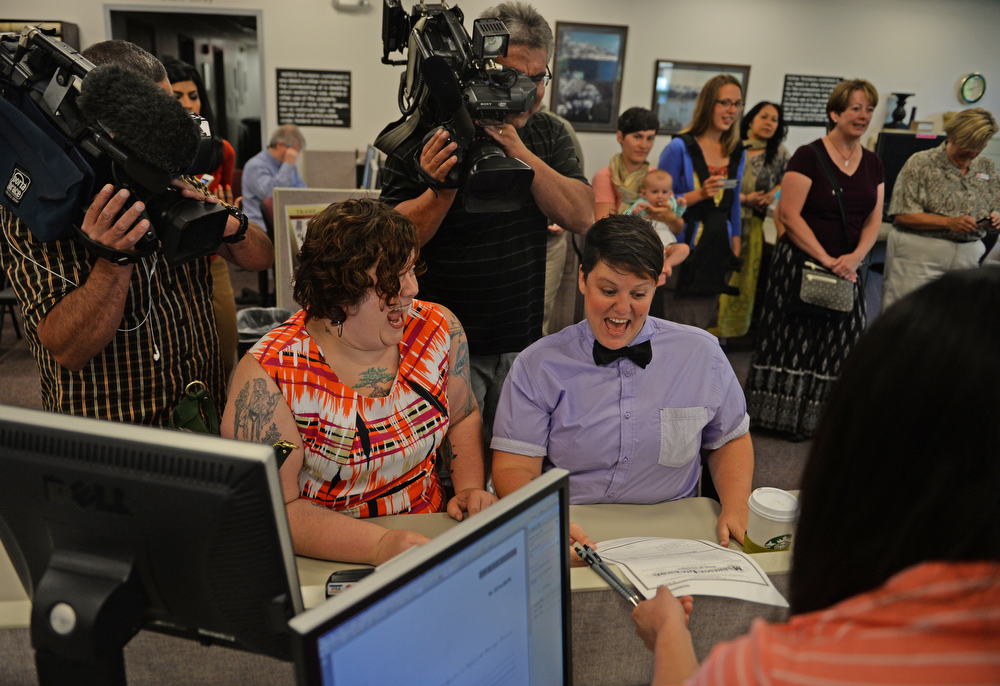. Newlyweds Andie Lyons, left, and Laurie Lynch celebrate getting their marriage license issued this morning at the Boulder County Clerk and Recorder\'s Office, June 26, 2014. Boulder County issued five more marriage licences to same-sex couples in the first hour that the Clerk and Recorder\'s Office in Boulder was open. (Photo by RJ Sangosti/The Denver Post)