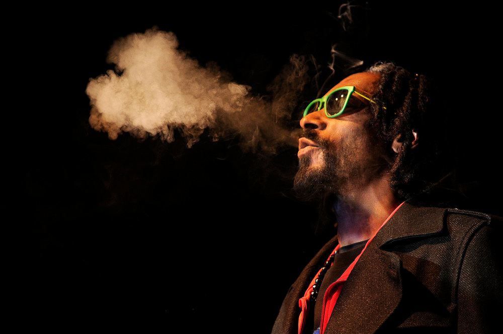 """. Snoop Lion exhales marijuana smoke while doing a Q&A with the audience after the screening of his documentary Reincarnated on Friday, April 19, 2013 at the Fillmore Auditorium in Denver during the first ever \""""Green Carpet\"""" event as a part of the High Times Cannabis Cup. High Times is presenting its first ever Cannabis Cup in Denver after the passage of Amendment 64. Seth A. McConnell, The Denver Post"""