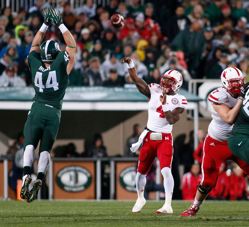 . Nebraska quarterback Tommy Armstrong Jr. (4) throws a pass over Michigan State\'s Marcus Rush (44) as Nebraska\'s Zach Sterup, right, blocks during the first quarter of an NCAA college football game, Saturday, Oct. 4, 2014, in East Lansing, Mich. (AP Photo/Al Goldis)