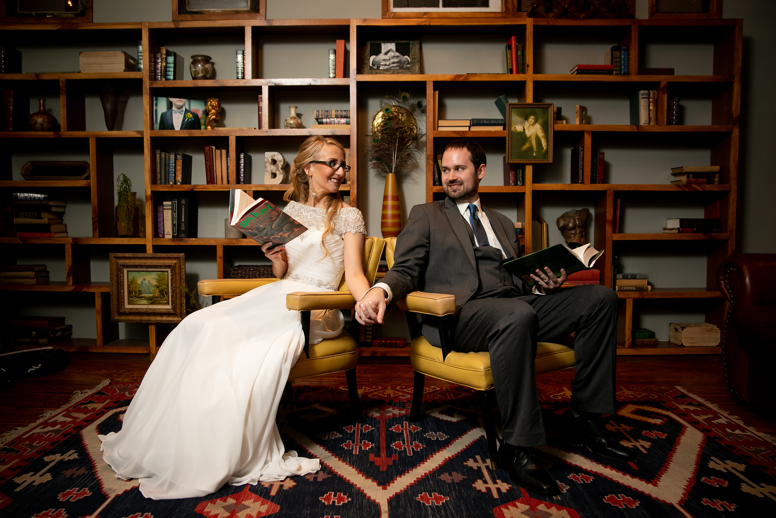 Bride and groom holding hands while sitting in a library style offices as they hold harry potter books