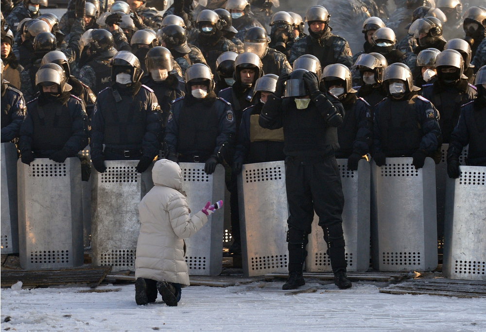 . A woman speaks as she kneels down in front of a line of riot police in the center of Kiev on January 24, 2014. Ukrainian protesters today expanded their protest camp in Kiev closer to the administration of President Viktor Yanukovych, after crisis talks to end Ukraine\'s worst crisis since its 1991 independence ended in deadlock. After five days of clashes that activists say left five dead, Ukraine\'s three main opposition leaders held several hours of talks with Yanukovych late on January 23 but the minor concessions they announced were greeted with derision by protesters. (SERGEI SUPINSKY/AFP/Getty Images)