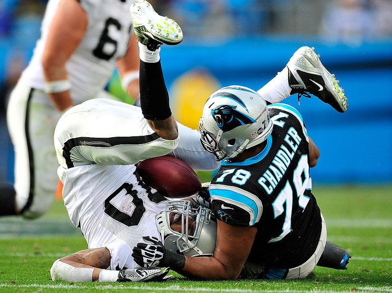 . Nate Chandler #78 of the Carolina Panthers upends Rod Streater #80 of the Oakland Raiders during play at Bank of America Stadium on December 23, 2012 in Charlotte, North Carolina. Carolina defeated Oakland 17-6. (Photo by Grant Halverson/Getty Images)