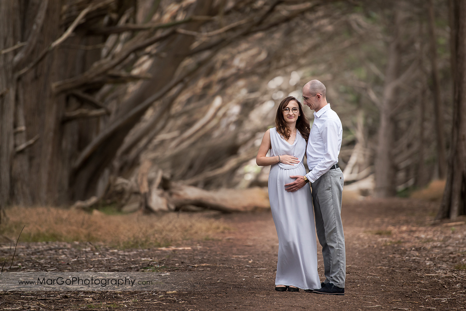 man looking at pregnant wife in long gray dress during Seal Cove Cypress Tree Tunnel maternity session