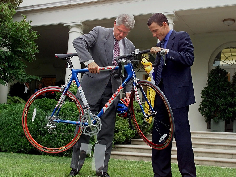 . President Clinton picks up a light-weight racing bicycle presented to him as a gift from the recent Tour de France victor, Lance Armstrong, in the Rose Garden of the White House in Washington, Tuesday, August 10, 1999. Armstrong, an American, was celebrated by the French as well as his own countrymen, because of his victory despite being a victim of cancer. (AP Photo/J. Scott Applewhite)