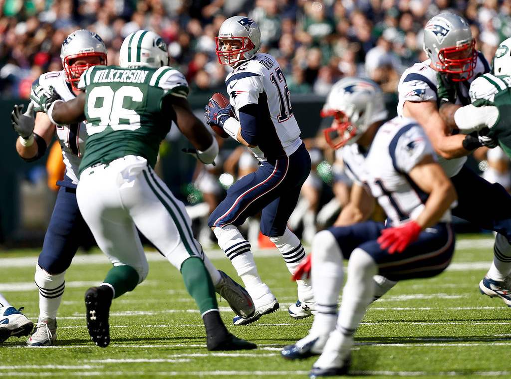 . Tom Brady #12 of the New England Patriots looks for an open man against the New York Jets during their game at MetLife Stadium on October 20, 2013 in East Rutherford, New Jersey.  (Photo by Jeff Zelevansky/Getty Images)