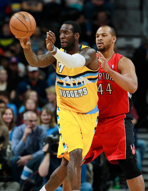 . Denver Nuggets forward J.J. Hickson, left, passes the ball as Toronto Raptors forward Chuck Hayes covers in the first quarter of an NBA basketball game in Denver, Friday, Jan. 31, 2014. (AP Photo/David Zalubowski)