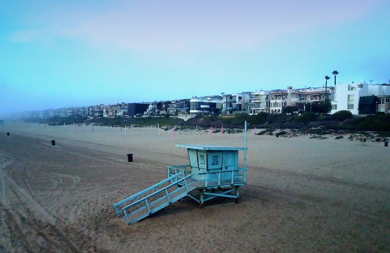 Looking down at a lifeguard station and the cityscape of Manhattan Beach, from the vantage point of the Manhattan Beach Pier