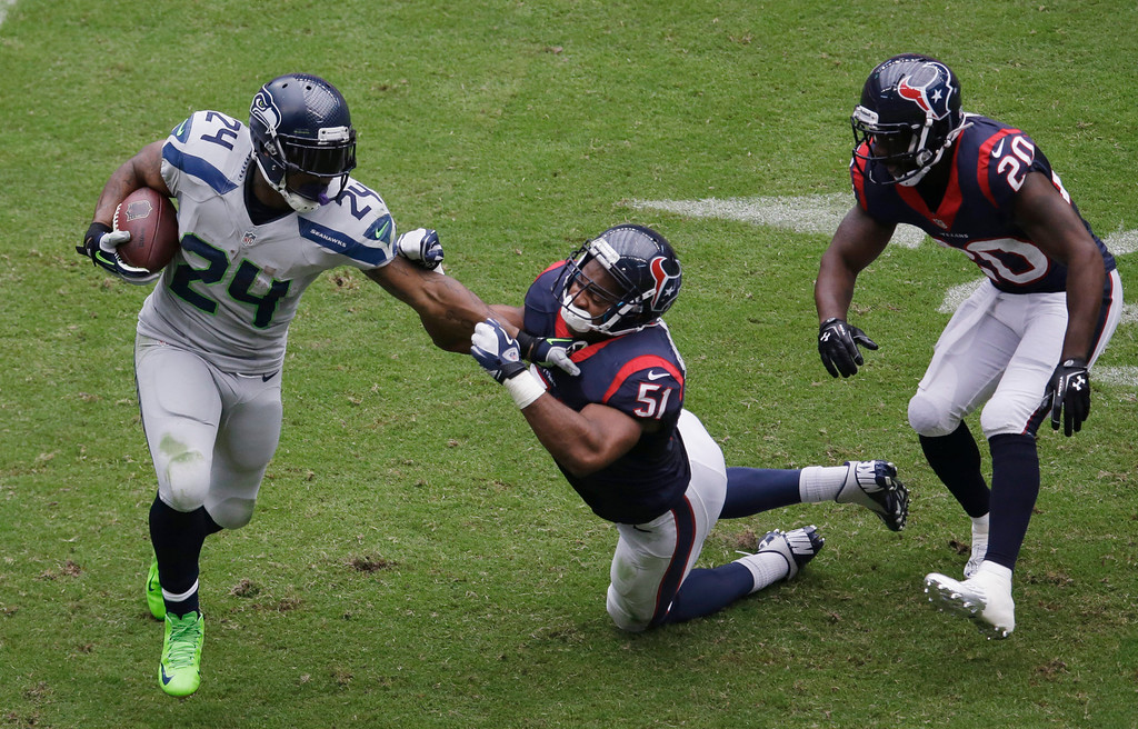 . Seattle Seahawks\' Marshawn Lynch (24) is pulled down by Houston Texans\' Darryl Sharpton (51) during the second quarter an NFL football game on Sunday, Sept. 29, 2013, in Houston. (AP Photo/David J. Phillip)