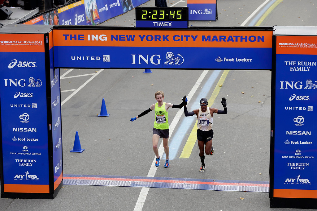 . American runners Michael Cassidy, left, and Meb Keflezighi cross the finish line holding hands  at the 2013 New York City Marathon in New York, Sunday, Nov. 3, 2013.  (AP Photo/Seth Wenig)