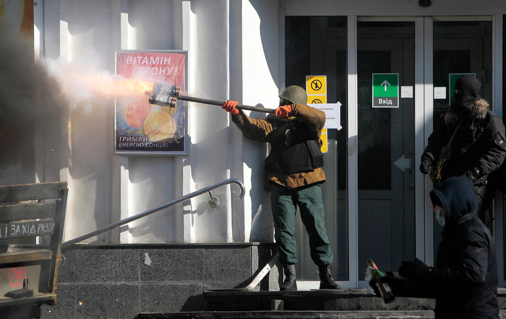 . An anti-government protester fires an improvised weapon during clashes with riot police  outside Ukraine\'s parliament in Kiev, Ukraine, Tuesday, Feb. 18, 2014.  Thousands of anti-government protesters clashed with police in a new eruption of violence Tuesday. (AP Photo/Sergei Chuzavkov)