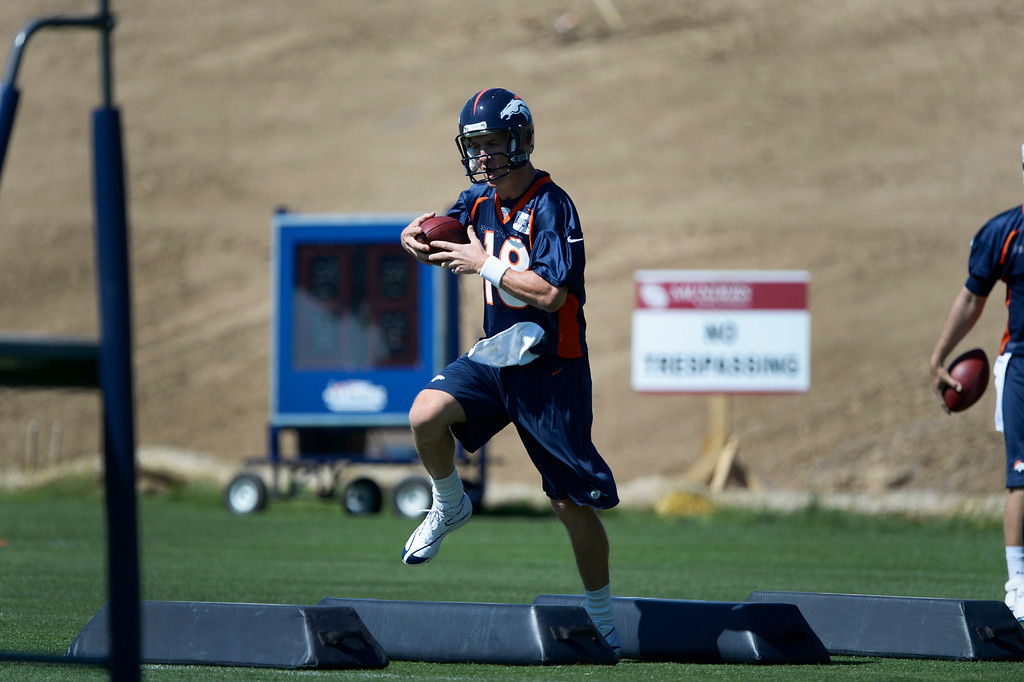 . Denver Broncos quarterback Peyton Manning (18) runs through drills during OTAs June 2, 2014 at Dove Valley. (Photo by John Leyba/The Denver Post)