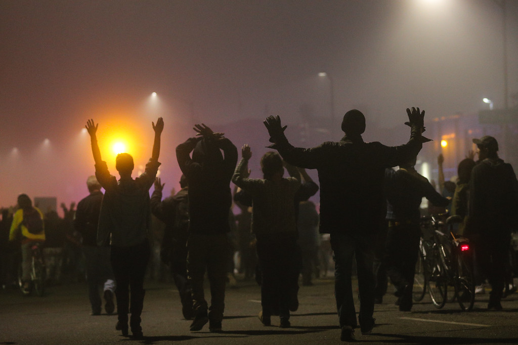 . Protesters walk through fog in East Oakland with their hands raised on the second night of demonstrations following a Staten Island, New York grand jury\'s decision not to indict a police officer in the chokehold death of Eric Garner on December 4, 2014 in Oakland, California. The grand jury declined to indict New York City Police Officer Daniel Pantaleo in Garner\'s death. (Photo by Elijah Nouvelage/Getty Images)