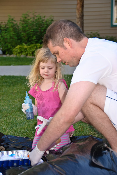 Keith helping Ella apply ink to her tye die shirt.