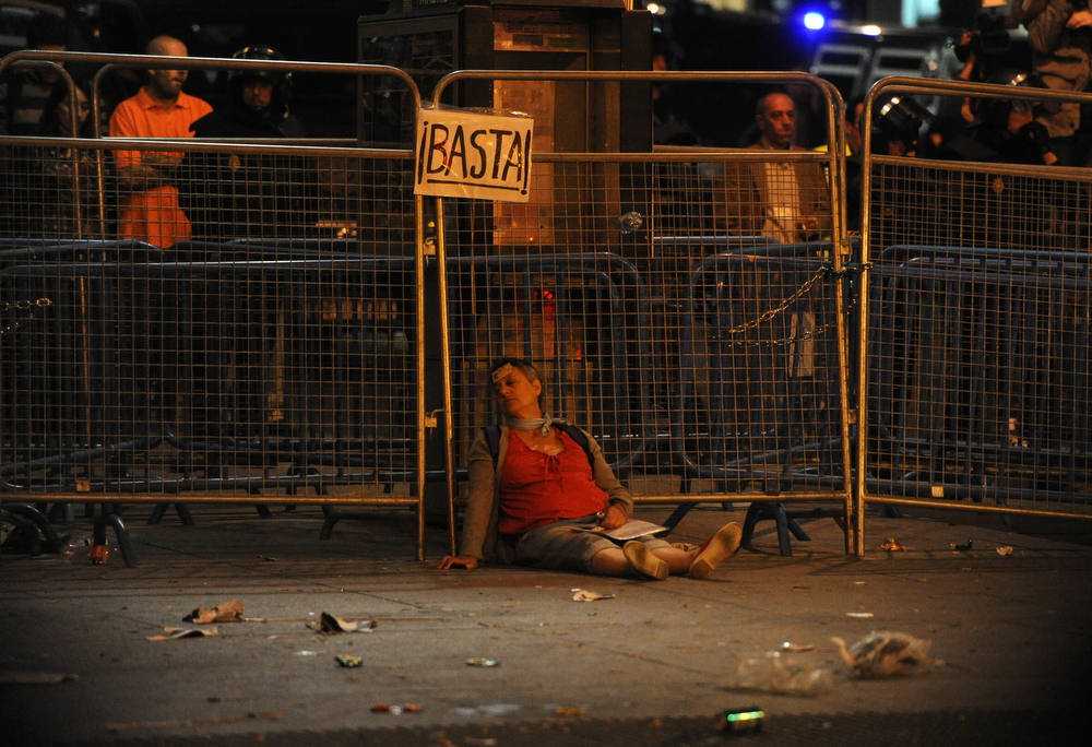 ". An injured woman lies on the street during a demonstration organized by Spain\'s ""indignant\"" protesters to decry an economic crisis they say has \""kidnapped\"" democracy, on September 25, 2012 in Madrid. Spanish riot police fired rubber bullets and baton-charged protesters as thousands rallied near parliament in Madrid in anger at the government\'s handling of the economic crisis.  AFP PHOTO / DOMINIQUE  FAGET/AFP/Getty Images"