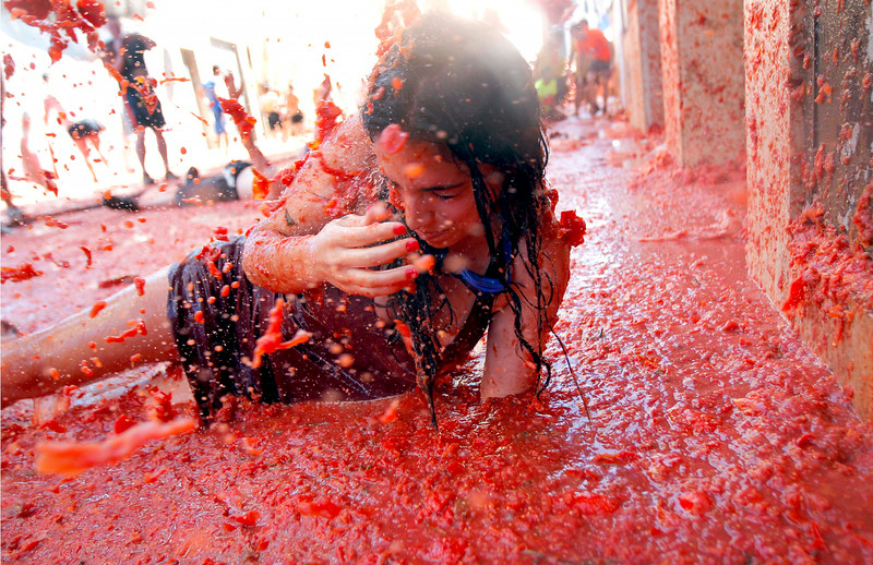". A woman lays in a puddle of tomato juice during the annual ""tomatina\"" tomato fight fiesta in the village of Bunol, 50 kilometers outside Valencia, Spain, Wednesday, Aug. 27, 2014. The streets of an eastern Spanish town are awash with red pulp as thousands of people pelt each other with tomatoes in the annual \""Tomatina\"" battle that has become a major tourist attraction. At the annual fiesta in Bunol on Wednesday, trucks dumped 125 tons of ripe tomatoes for some 22,000 participants, many from abroad to throw during the hour-long morning festivities. (AP Photo/Alberto Saiz)"