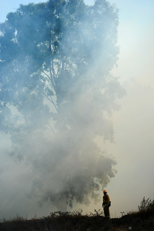 . A firefighter monitors a brushfire in the Sepúlveda Basin, Friday, August 22, 2014. (Photo by Michael Owen Baker/Los Angeles Daily News)