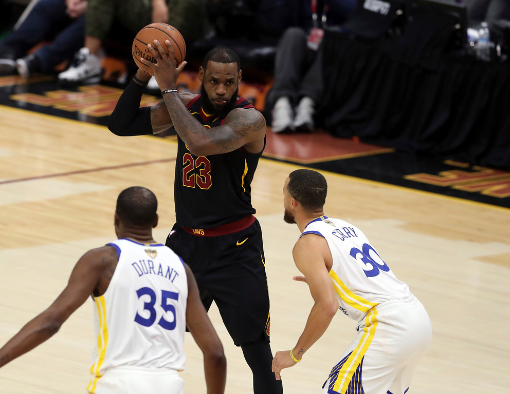 . Cleveland Cavaliers\' LeBron James looks to pass  the ball as Golden State Warriors\' Stephen Curry, right, and Kevin Durgant defend during the first half of Game 3 of basketball\'s NBA Finals, Wednesday, June 6, 2018, in Cleveland. (AP Photo/Carlos Osorio)