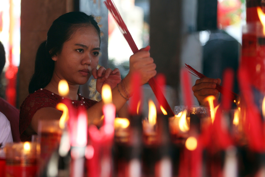 . A ethnic Chinese woman lights incense sticks during celebrations of the Lunar New Year at a temple in Bali, Indonesia, Friday, Feb. 16, 2018. The celebration marked the beginning of the Year of the Dog in Chinese calendar. (AP Photo/Firdia Lisnawati)