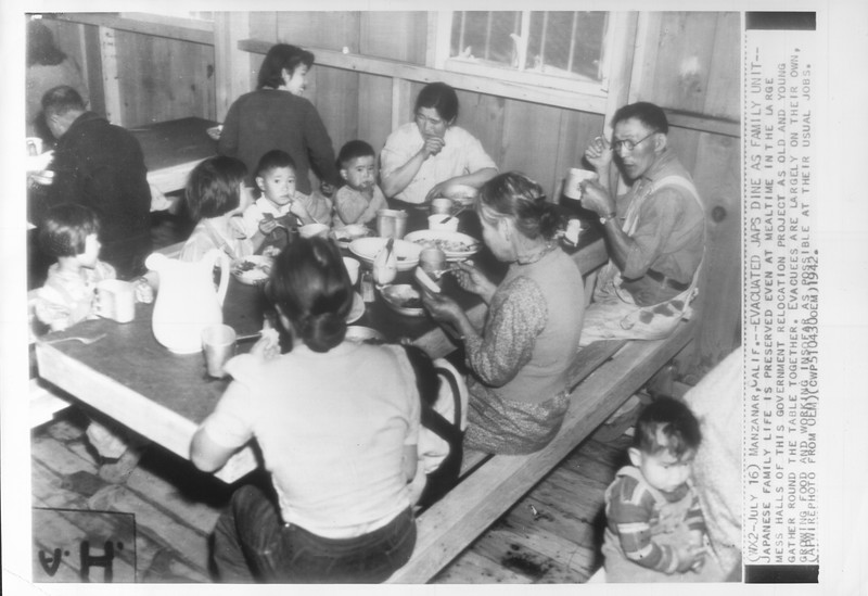 """""""Evacuated Japs Dine As Family Unit -- Japanese family life is preserved even at mealtime in the large mess halls of this government relocation project"""" -- caption on photograph"""
