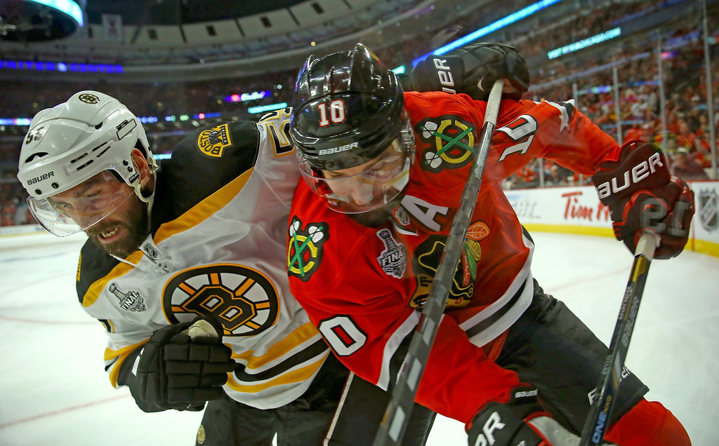 . CHICAGO, IL - JUNE 15:  Johnny Boychuk #55 of the Boston Bruins comes into contact with Patrick Sharp #10 of the Chicago Blackhawks in Game Two of the NHL 2013 Stanley Cup Final at United Center on June 15, 2013 in Chicago, Illinois.  (Photo by Bruce Bennett/Getty Images)