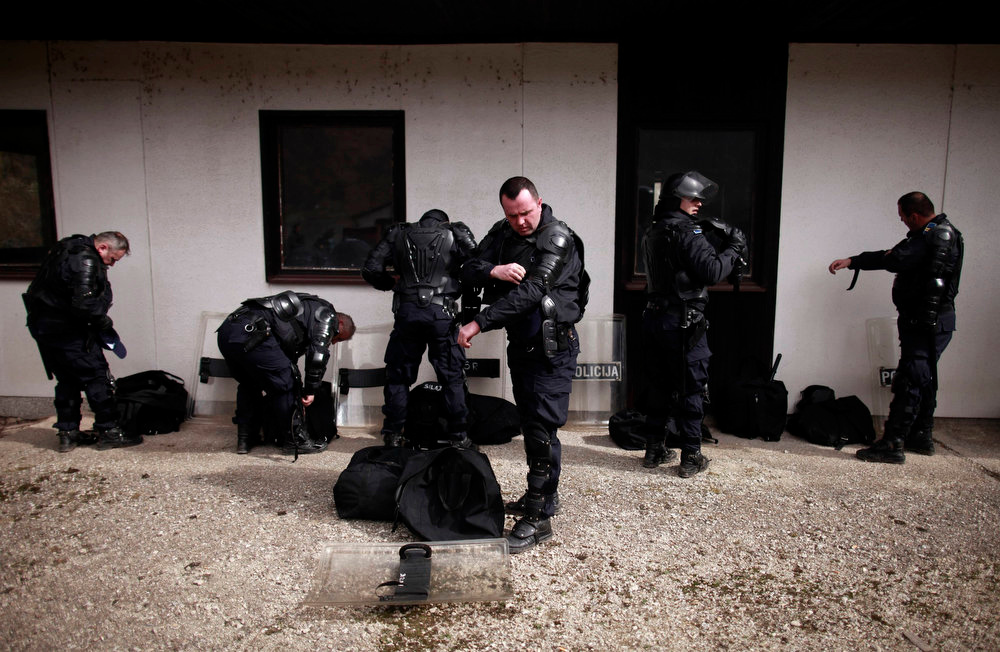 . Members of Special Police Force from the city of Zenica remove equipment after an anti soccer hooligan exercise with people role-playing as demonstrators in Nemila, March 18, 2013. The local police organized a final exercise in preparation against soccer hooliganism for the upcoming World Cup qualifier soccer match between Greece and Bosnia on March 22. According to local media, local police are anticipating violence which may arise among Serbian supporters, who support the Greek team, and Bosnian fans.  REUTERS/Dado Ruvic