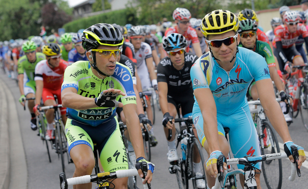 . Spain\'s Alberto Contador, left, gestures when talking to Kazakhstan\'s Maxim Iglinskiy, right, during the ceremonial procession prior to the start of the eighth stage of the Tour de France cycling race over 161 kilometers (100 miles) with start in Tomblaine and finish in Gerardmer, France, Saturday, July 12, 2014. Center rear in black is Australia\'s Richie Porte. (AP Photo/Laurent Cipriani)