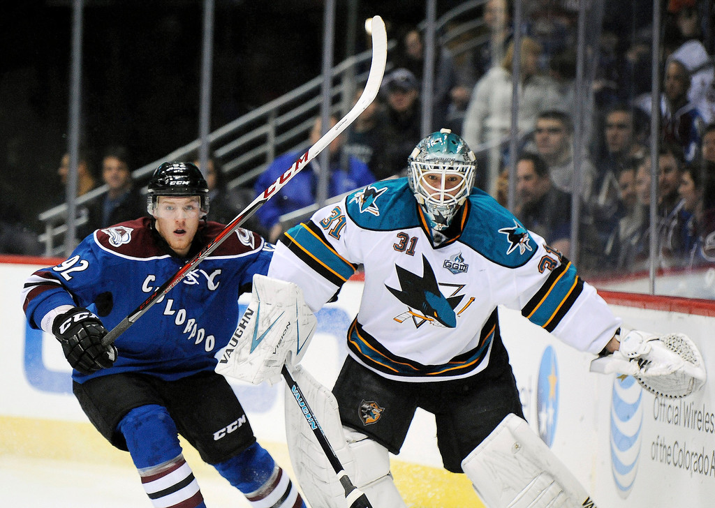 . Colorado Avalanche left wing Gabriel Landeskog, left, of Sweden, and San Jose Sharks goalie Antti Niemi, of Finland, watch the puck in the first period of an NHL hockey game on Sunday, March 10, 2013, in Denver.  (AP Photo/Chris Schneider)