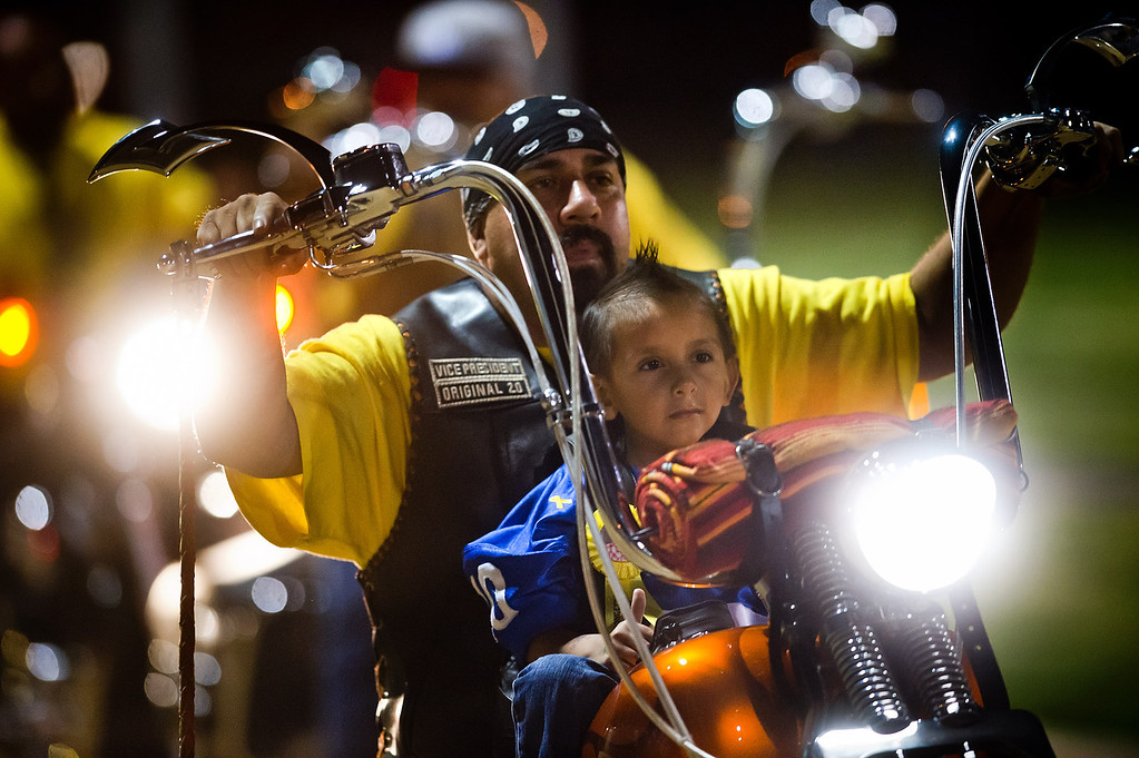 . Doryan Torres, 5, rides with Eirc Montano, of La Puente, as he is presented during the El Monte High School football halftime special in El Monte on Friday night, Sept. 13, 2013. Torres who is turning 6 on Saturday, has been battling a brain tumor since he was 14 months old. (Photo by Watchara Phomicinda/ San Gabriel Valley Tribune)