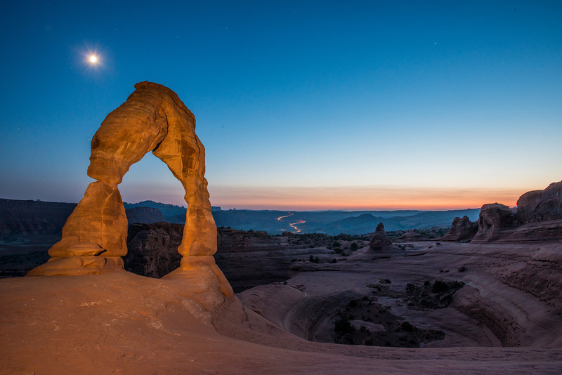 Delicate arch with the moon and cars leaving zion