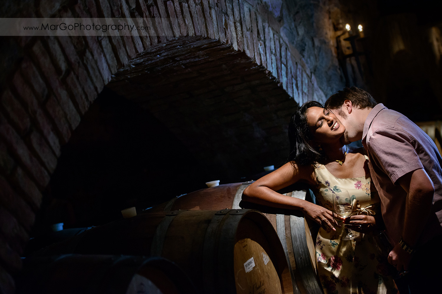 man in pink shirt kissing Indian woman in flower dress kissing in the wine cellar during engagement session at Castello di Amorosa in Calistoga