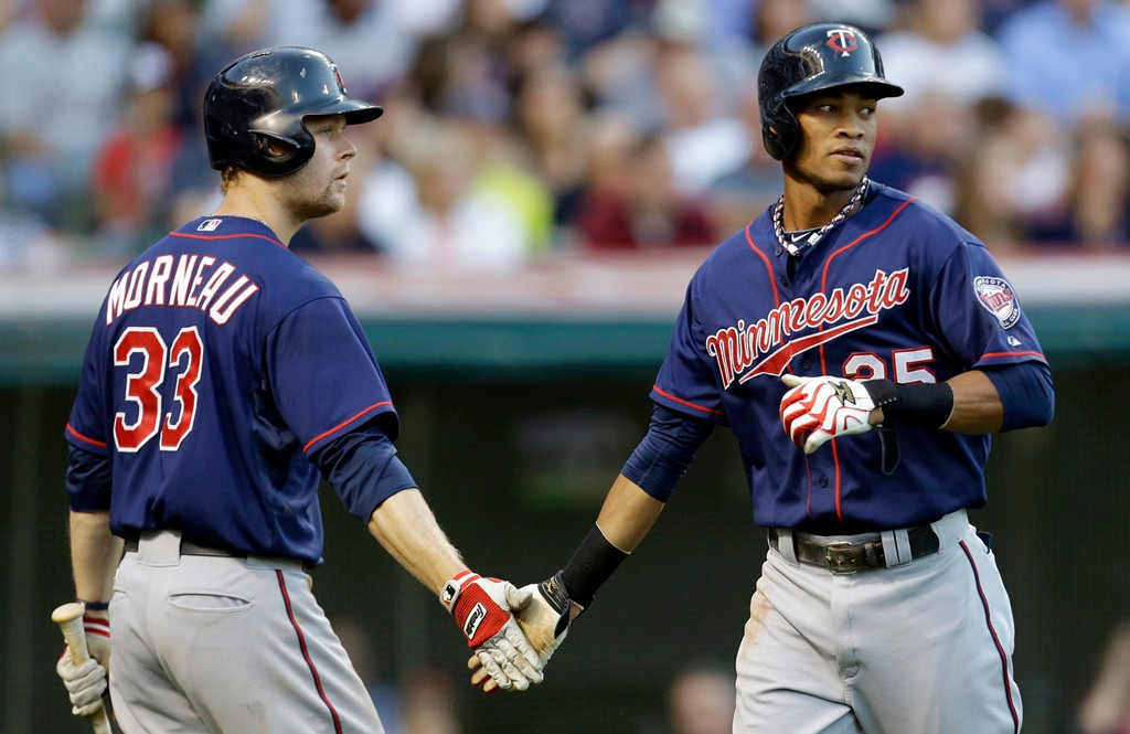 . Minnesota\'s Pedro Florimon, right, slaps hands with Justin Morneau after scoring on a Chris Herrmann double in the second inning against the Indians. (AP Photo/Tony Dejak)