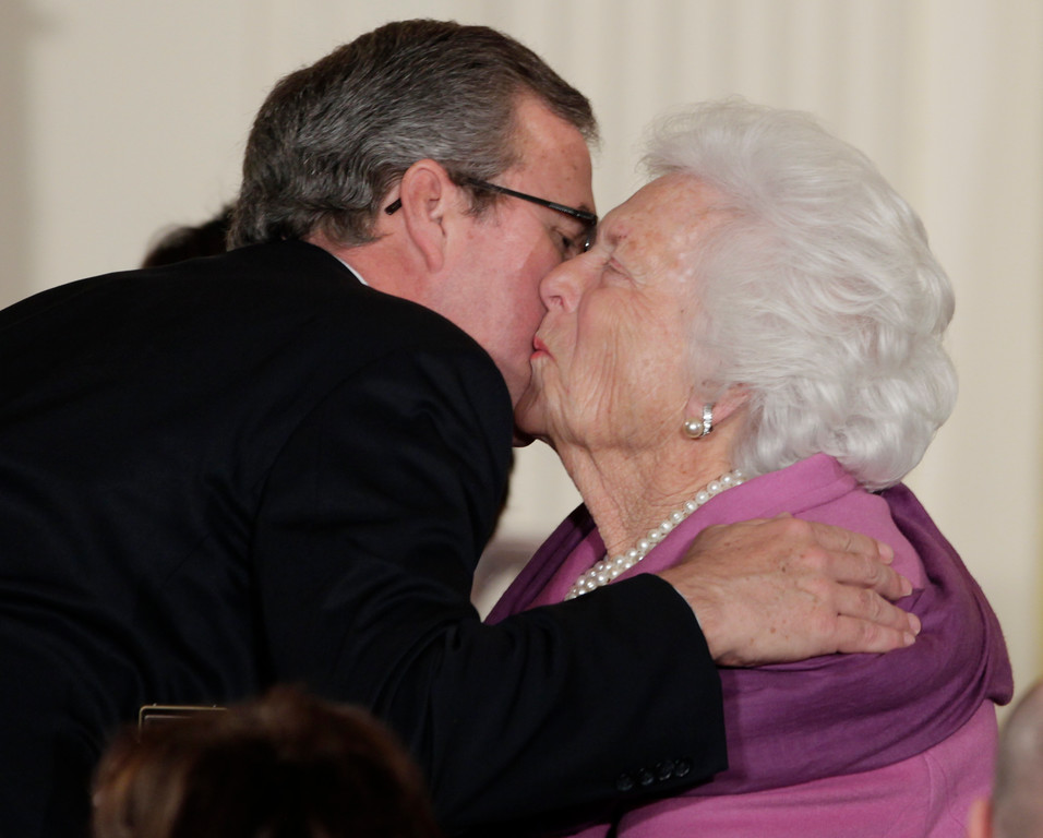 . Former first lady Barbara Bush, right, greets her son former Florida Gov. Jeb Bush, with a kiss as she arrives a the 2010 Presidential Medal of Freedom ceremony, Tuesday, Feb. 15, 2011, in the East Room of the White House in Washington. Former President George H.W. Bush will receive the Medal. (AP Photo/Carolyn Kaster)