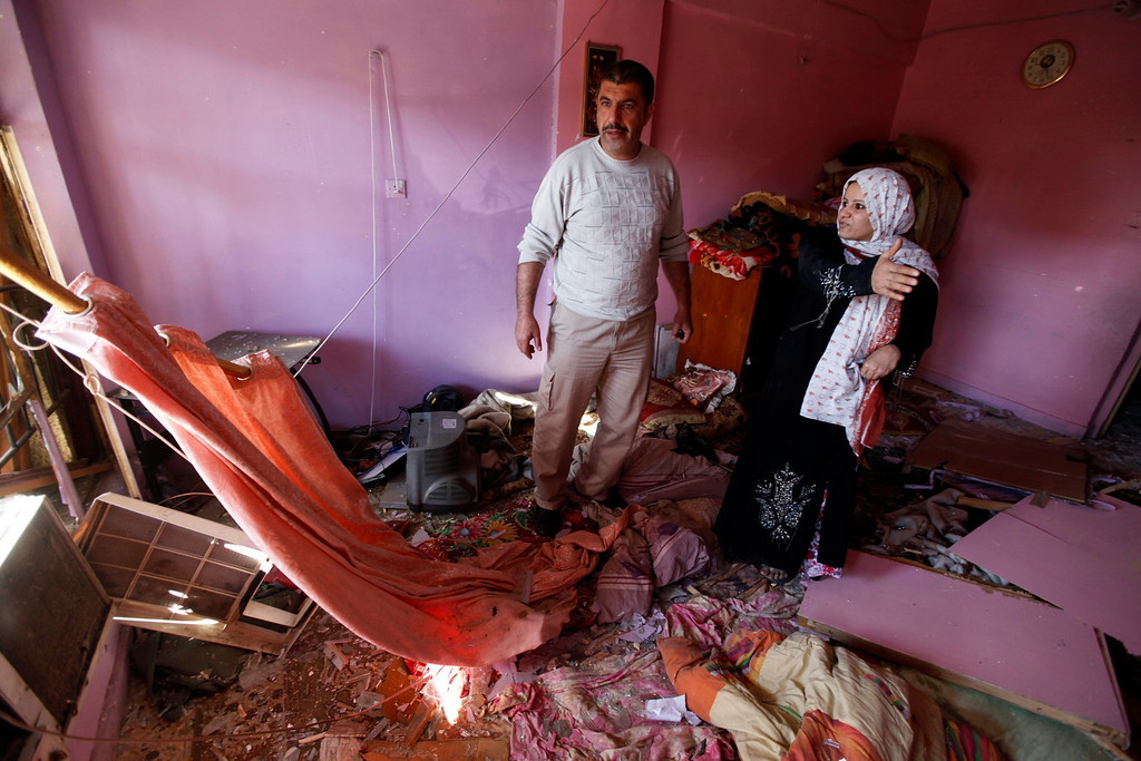 . Iraqis examine damage inflicted on their house by a car bomb attack in AL-Mashtal district in Baghdad March 19, 2013.   REUTERS/Mohammed Ameen